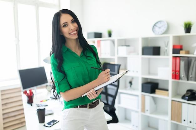 Une jeune femme dans le bureau tient un crayon et une feuille de notes.