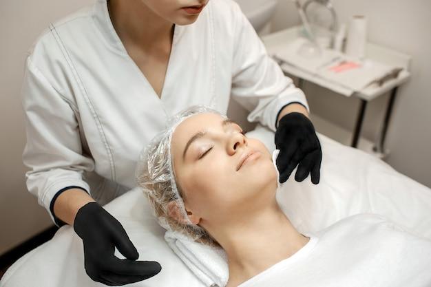 Jeune femme, dans, casquette, coucher divan, dans, room. l'esthéticienne se tient debout et fait les procédures avec les mains. profitez-en et détendez-vous.