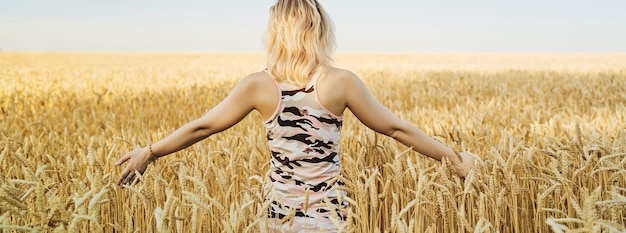 Jeune femme dans un champ de blé. fille en robe marchant dans le champ et touche le blé. concept de récolte riche. bannière avec espace de copie.