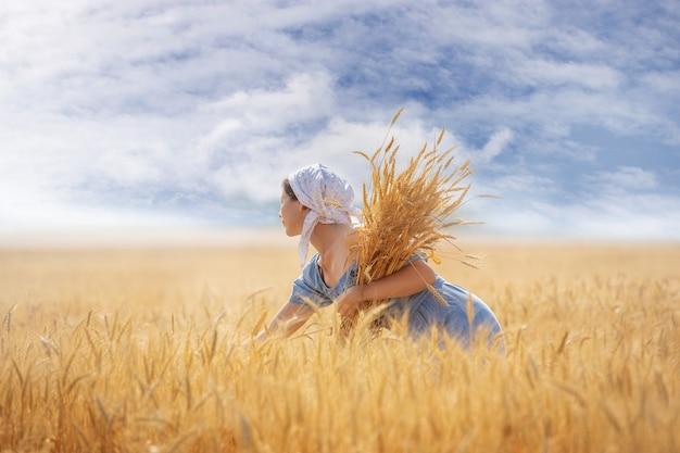 Une jeune femme dans un champ de blé avec des oreilles dans ses mains