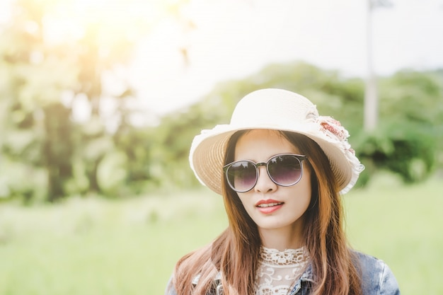 Jeune femme dans un champ, des lunettes de soleil arrondies s'amuser en plein air dans la campagne.