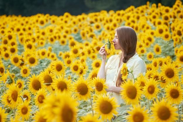 Jeune femme dans le champ de tournesols s'amuse