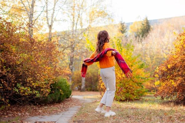 Une jeune femme dans un chandail orange s'enveloppe dans une écharpe dans un parc d'automne