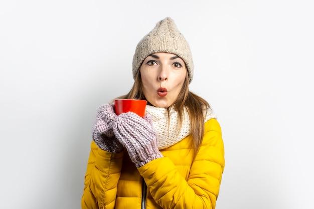 Jeune femme dans un chapeau chaud et sourires mitaines isolés