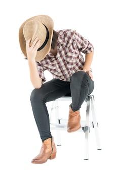 Jeune femme dans un chapeau de cowboy et chemise à carreaux avec la main sur son chapeau
