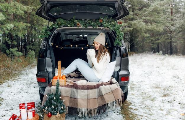 Une jeune femme dans un chapeau de laine est assise dans le coffre d'une voiture et tient une tasse de thé chaud
