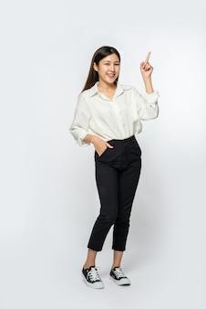 Une jeune femme dans une chemise blanche et pointant vers le haut