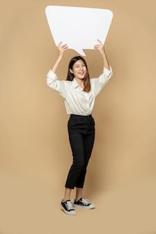 Une jeune femme dans une chemise blanche tenant un symbole de boîte de pensée
