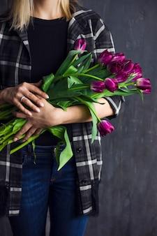 Jeune femme, dans, chemise écossaise, tenant, bouquet, de, terry violet, tulipes, fond sombre