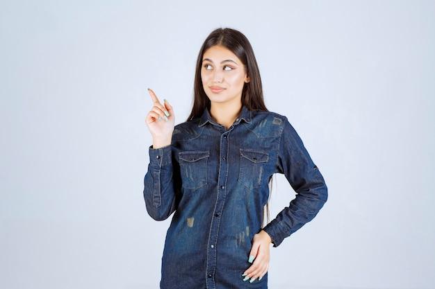 Jeune femme dans une chemise en jean pointant vers la gauche avec les émotions du visage