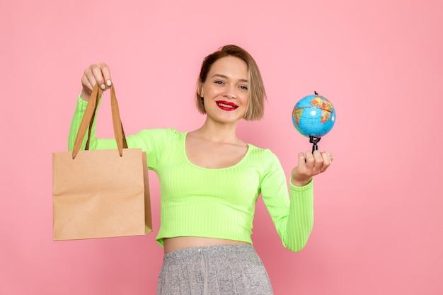 Jeune femme, dans, chemise verte, et, jupe grise, tenue, paquet, et, petit globe