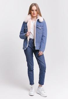 Jeune femme dans un costume en jean avec un col de fourrure sur fond blanc