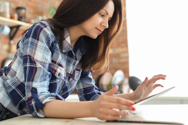 Jeune femme dans la cuisine à l'aide de tablette numérique.