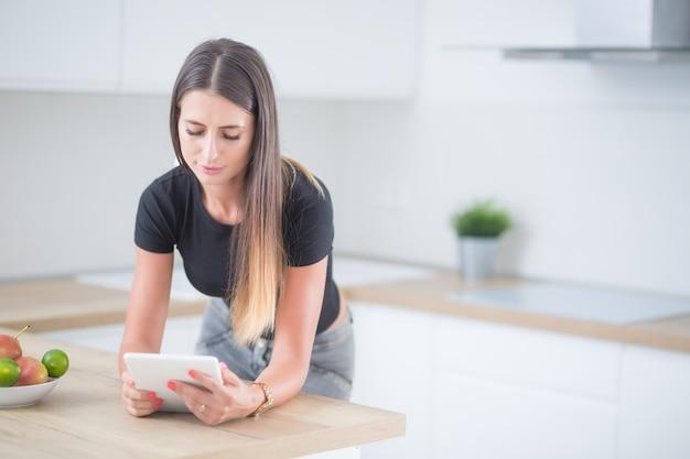 Jeune femme dans la cuisine à domicile avec tablette.