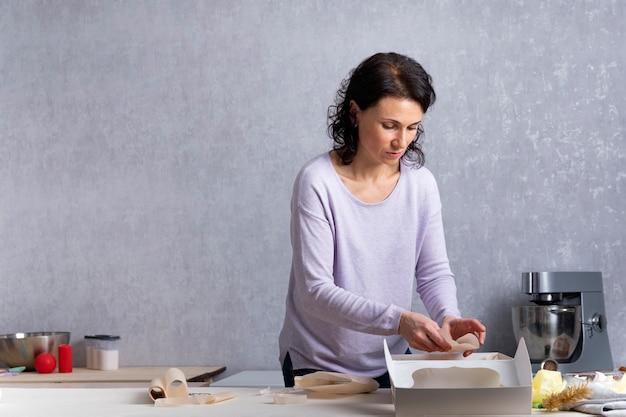Jeune femme dans la cuisine est l'emballage des pâtisseries dans une boîte en carton blanc. processus d'emballage.