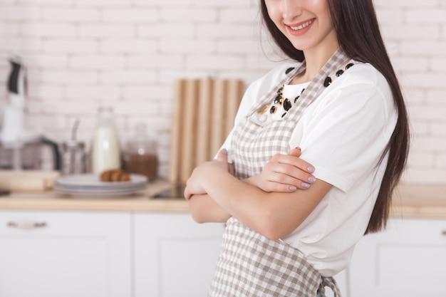 Jeune femme dans la cuisine. femme au foyer, debout dans la cuisine. cuisine féminine.