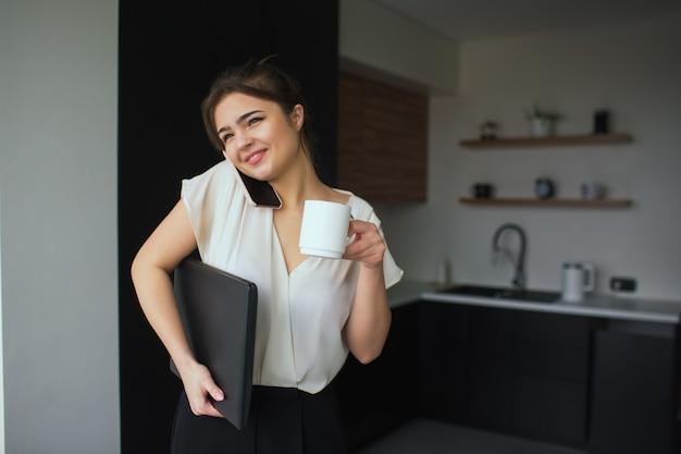 Jeune femme dans la cuisine pendant la quarantaine. femme d'affaires, parler au téléphone dans le bureau à domicile pendant le travail à distance. fille tenir une tasse blanche et un ordinateur portable noir.