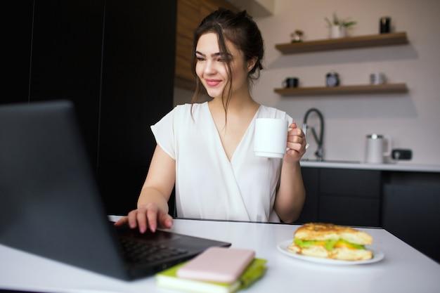 Jeune femme dans la cuisine pendant la quarantaine. fille assise à table et à l'aide d'un ordinateur portable. tenez la tasse blanche à la main. travail à distance du bureau à domicile.