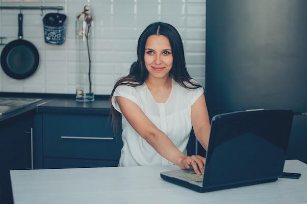 Jeune femme dans la cuisine travaillant avec un ordinateur portable