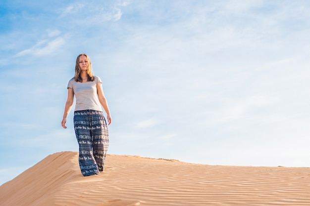 Jeune femme dans le désert de sable rad au coucher du soleil ou à l'aube