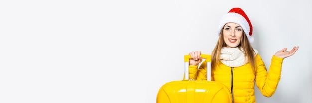 Jeune femme dans une doudoune jaune et un chapeau isolé