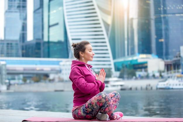 Une jeune femme dans easy seat pose contre la ville et la rivière