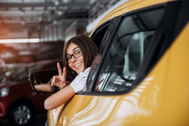 Jeune femme, dans, elle, nouvelle voiture, sourire