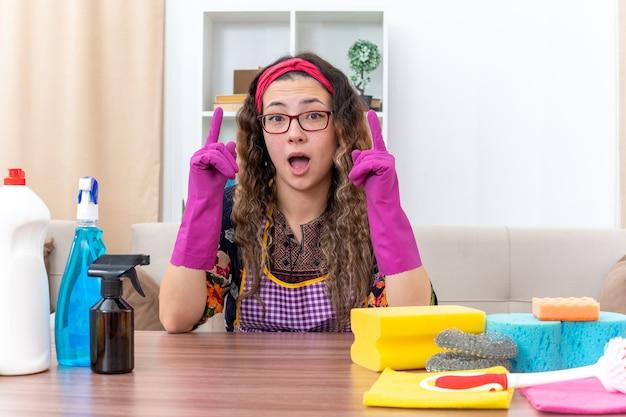 Jeune femme dans des gants en caoutchouc à la surprise et heureuse assise à la table avec des produits de nettoyage et des outils dans un salon lumineux