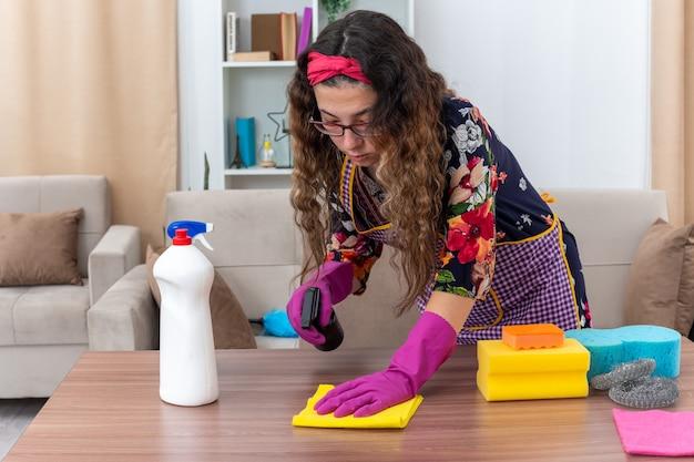 Jeune femme dans des gants en caoutchouc tenant un spray de nettoyage et une table de nettoyage de chiffon à l'aise dans un salon lumineux