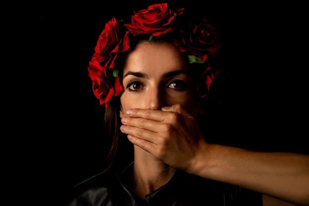 Jeune femme dans une guirlande de fleurs, couvrant sa bouche avec sa paume