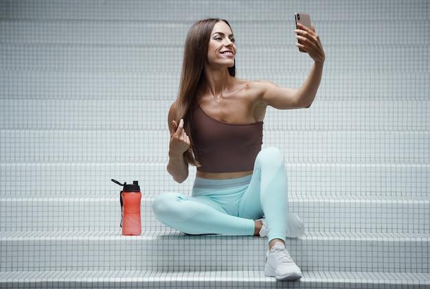 Jeune femme, dans, gymnase, mode de vie sain, regarder, les, téléphone portable