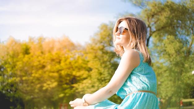 Jeune femme dans un jardin ensoleillé. journée d'été en plein air. concept de méditation et de liberté