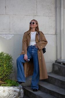 Jeune femme dans un long manteau à la mode se promène dans la ville d'automne.
