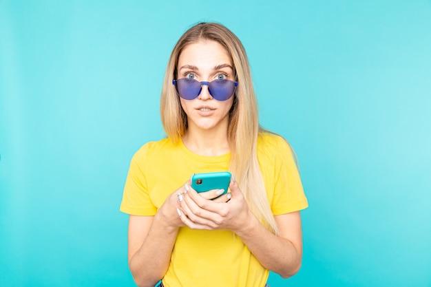 Jeune femme, dans, lunettes noires, debout, sur, bleu, isolé, regarder appareil-photo