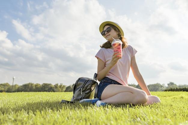 Jeune femme, dans, lunettes soleil, et, chapeau, boissons, été, baie, boisson