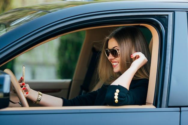 Jeune femme, dans, lunettes soleil, derrière, les, volant