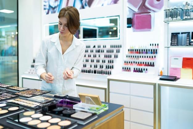 Jeune femme dans un magasin de cosmétiques teste les ombres à paupières et la poudre pour le visage