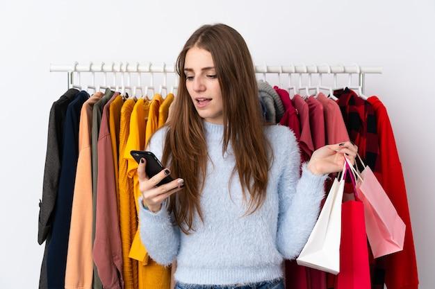 Jeune femme dans un magasin de vêtements avec un mobile
