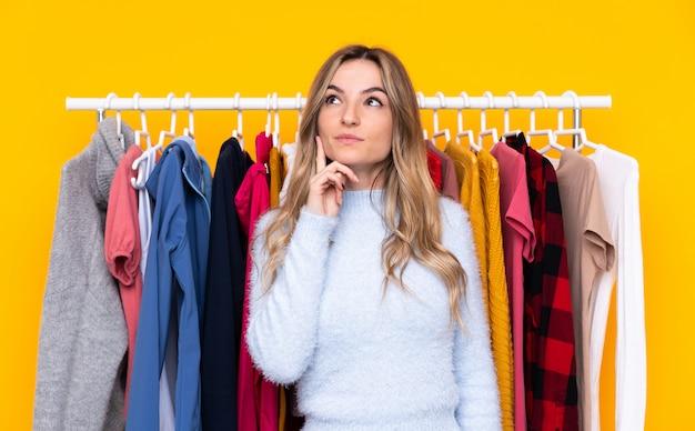 Jeune femme dans un magasin de vêtements sur un mur jaune isolé en pensant à une idée