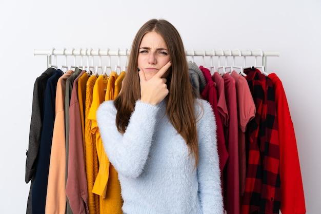 Jeune femme dans un magasin de vêtements en pensant à une idée