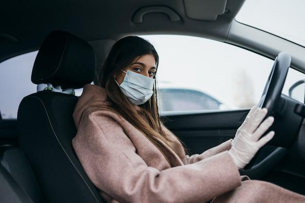 Jeune femme dans un masque et des gants au volant d'une voiture.