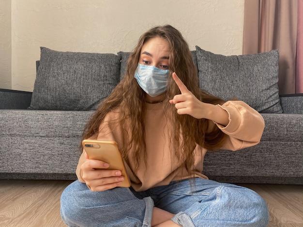 Jeune femme dans un masque médical communique sur skype assis à la maison