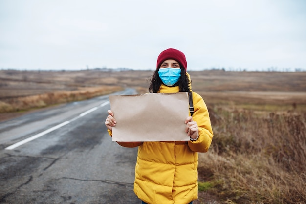 Jeune femme dans un masque médical portant une veste jaune et un chapeau rouge se dresse avec une affiche en papier vierge sur le côté d'une route vide.