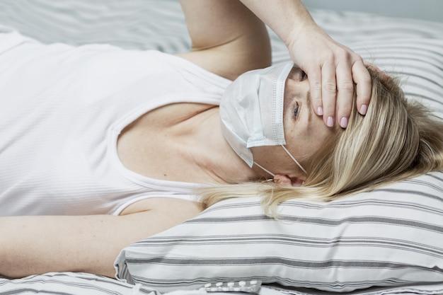 Une jeune femme dans un masque médical se trouve sur un lit avec une température élevée.
