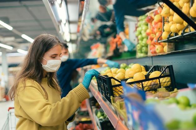 Jeune femme dans un masque de protection choisissant des citrons dans un magasin. coronavirus en ville