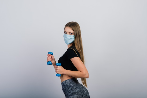 Jeune femme dans un masque de protection avec des haltères. sports en quarantaine, convoitise.
