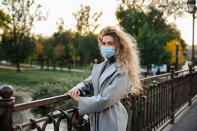 Une jeune femme dans un masque de protection se dresse sur le pont. concept de pandémie et de soins de santé du coronavirus covid-19. précautions face au coronavirus