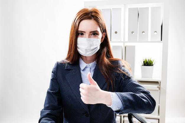 Jeune femme dans un masque de protection travaille au bureau à l'ordinateur