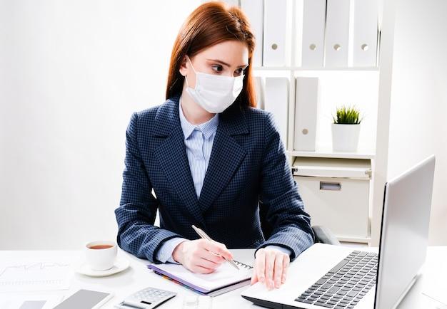 Une jeune femme dans un masque de protection travaille sur un ordinateur. femme d'affaires dans un masque médical au bureau.