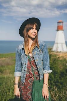 Jeune femme dans la nature, phare, tenue bohème, veste en jean, chapeau noir, souriant, heureux, été, accessoires élégants